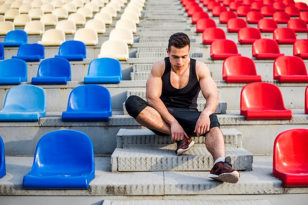 Junger männlicher athlet der eignung, der auf der tribüne sich entspannt