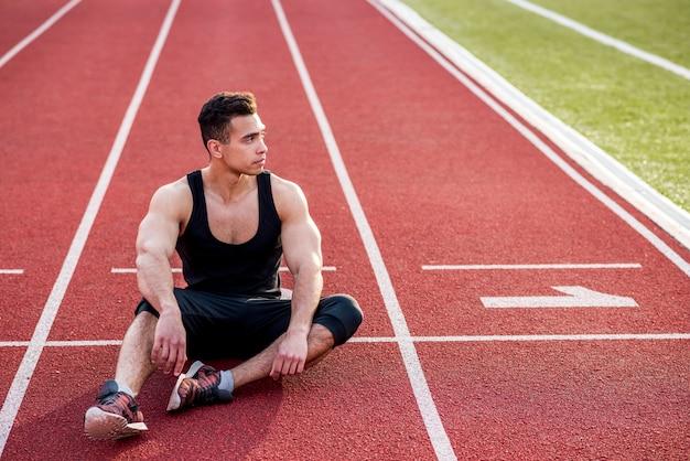 Junger männlicher athlet der eignung, der auf roter rennstrecke im stadion sich entspannt