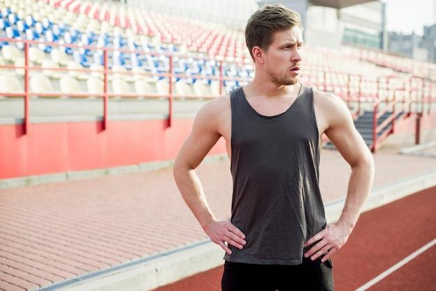 Junger männlicher athlet der eignung mit seinen händen auf der hüfte, die vor arena steht