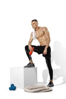 Junger männlicher athlet posiert auf weiß mit schatten
