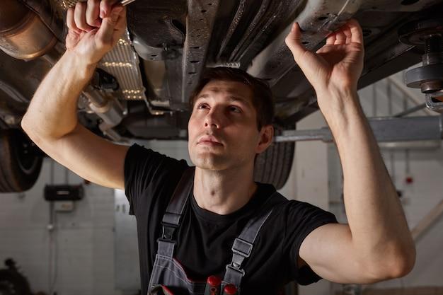 Junger männlicher automechaniker in der uniform, die auto im autodienst prüft