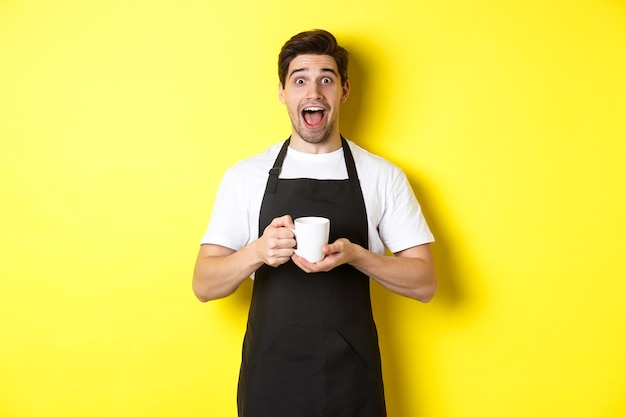 Junger männlicher barista, der kaffeetasse hält und überrascht aussieht, in schwarzer schürze vor gelbem hintergrund stehend