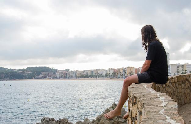 Junger männlicher bart, langes haar, das freizeitkleidung sitzt, sitzt auf einem felsen, der in die ferne auf einem lloret de mar, costa brava, katalonien, spanien auf dem hintergrund schaut.
