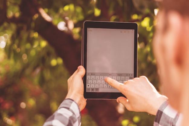 Junger männlicher bauer, der ein smartphone oder ein tablet verwendet, um die ernte im garten zu zählen