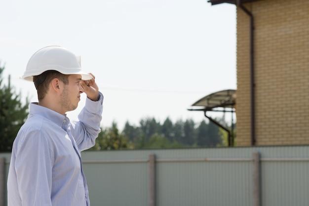 Junger männlicher bauingenieur mit weißem kopfschutz, der die website besucht, um bauaktualisierungen zu überwachen.