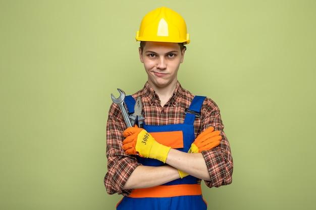 Junger männlicher baumeister, der uniform mit handschuhen trägt, die einen gabelschlüssel isoliert auf olivgrüner wand halten