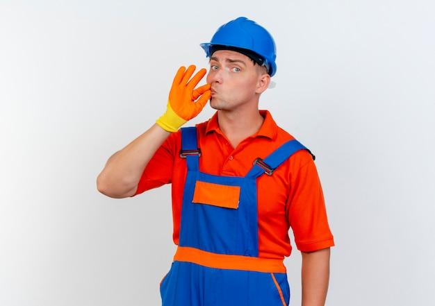 Junger männlicher baumeister, der uniform und schutzhelm in handschuhen trägt, die köstliche geste zeigen