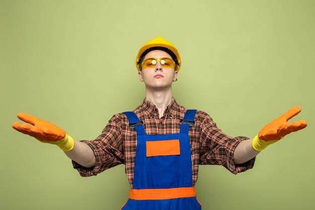 Junger männlicher baumeister in uniform und handschuhen mit brille isoliert auf olivgrüner wand