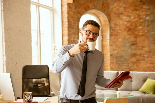 Junger männlicher büroangestellter, der kaffee im büro trinkt