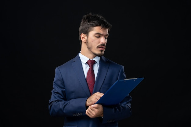 Junger männlicher büroangestellter im anzug, der dokumente an isolierter dunkler wand hält