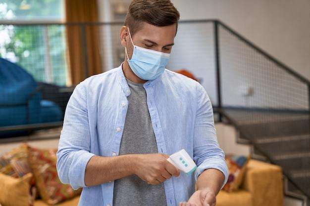 Junger männlicher büroangestellter mit medizinischer schutzmaske, der im büro steht und überprüft