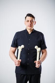 Junger männlicher chefarzt in einem schwarzen op-anzug. nahaufnahmeportrait. hält einen oberschenkelknochen in seinen händen. isoliert auf weißem hintergrund.