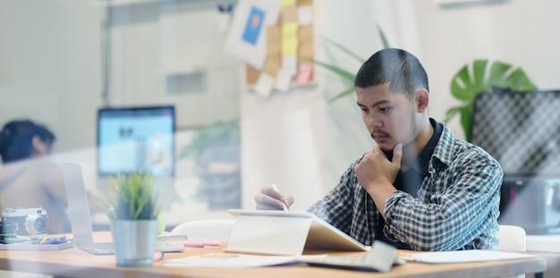 Junger männlicher designer, der an seinem projekt bei der anwendung der tablette arbeitet