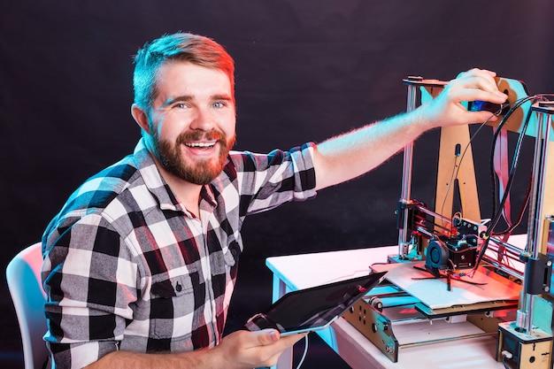 Junger männlicher designer-ingenieur, der einen drucker im labor verwendet und einen produktprototyp, ein technologie- und innovationskonzept studiert.