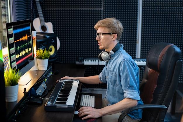 Junger männlicher dj im jeanshemd, der tonmischungs-tracls auf computerbildschirm beim sitzen am schreibtisch vor dem monitor betrachtet