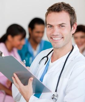 Junger männlicher doktor, der an der kamera lächelt