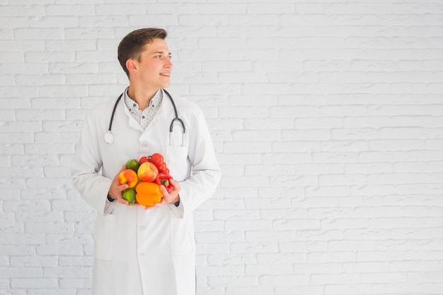 Junger männlicher doktor, der gegen die wand hält das gesunde lebensmittel weg schaut steht