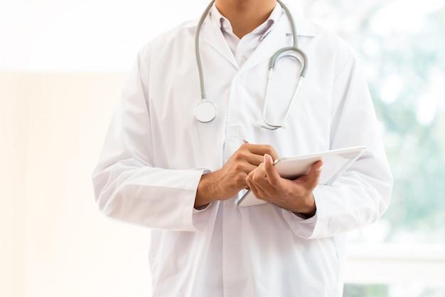 Junger männlicher doktor, der tablet-computer mit tragendem stethoskop der weißen kleiderreihe auf hals für das suchen von informationen behandelt patienten im krankenhaus oder in der klinik, medizinisches konzept des gesundheitswesens verwendet