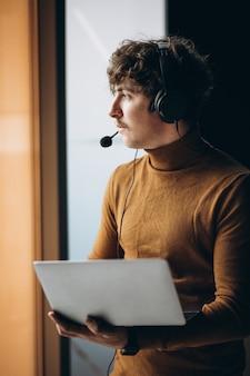 Junger männlicher dolmetscher, der am laptop arbeitet