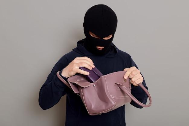 Junger männlicher einbrecher stiehlt frauenhandtasche