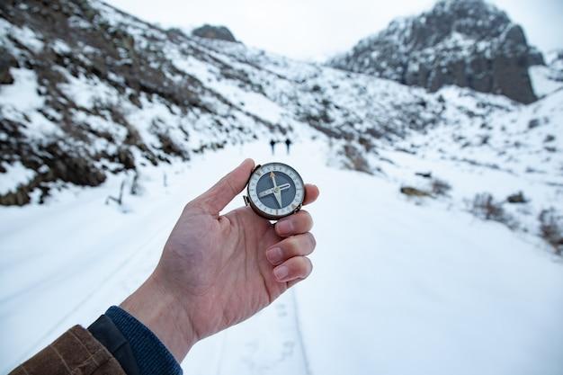 Junger männlicher entdecker, der einen kompass in der hand hält und die richtungen im winterwald sucht.