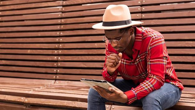 Junger männlicher erwachsener, der sitzt und liest