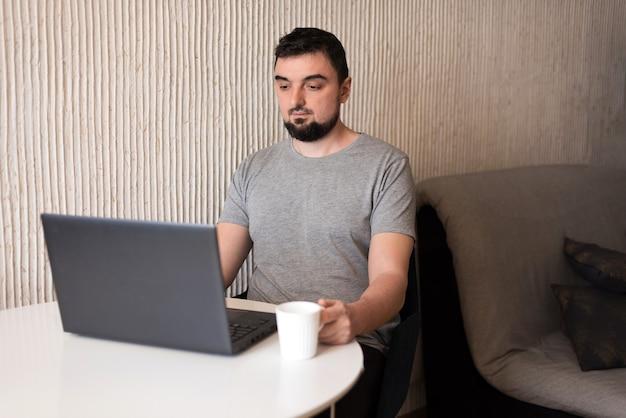 Junger männlicher fachmann, der zu hause computer verwendet