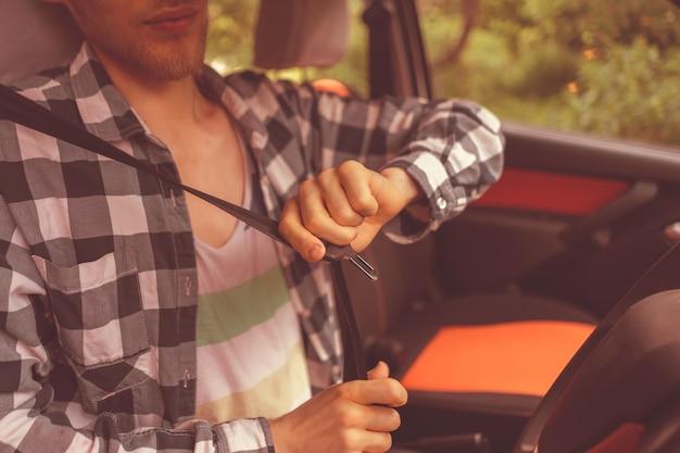 Junger männlicher fahrer, der den autosicherheitsgurt anlegt