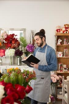 Junger männlicher florist, der im blumenladenschreiben im tagebuch mit stift steht