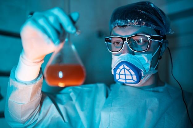 Junger männlicher forscher, der wissenschaftliches experiment durchführt.