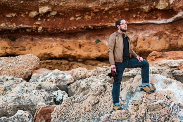 Junger männlicher fotograf, der auf einem felsenstrand mit kamera in seinen händen steht