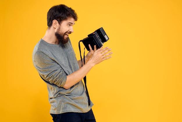 Junger männlicher fotograf mit einer alten filmkamera in seinen händen, die emotional aufwirft