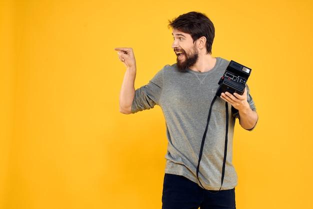 Junger männlicher fotograf mit einer alten filmkamera in seinen händen Premium Fotos