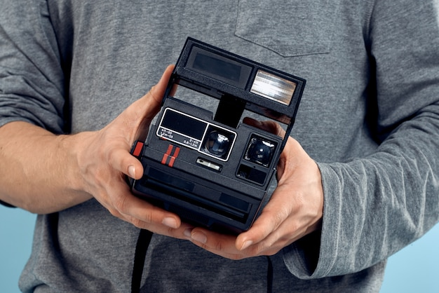 Junger männlicher fotograf mit einer alten kamera auf einer hellblauen wand, die emotional aufwirft