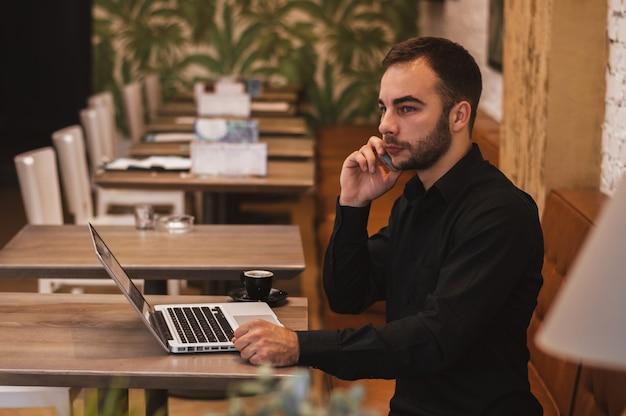 Junger männlicher freiberufler, der am handy beim sitzen der offenen laptop-computer der front im café plaudert
