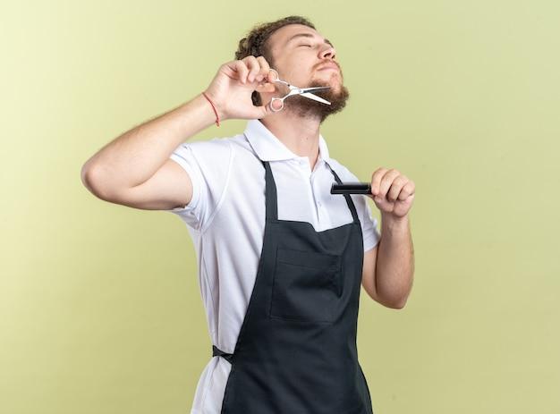 Junger männlicher friseur, der einen einheitlichen bart mit einer schere trägt, isoliert auf olivgrünem hintergrund