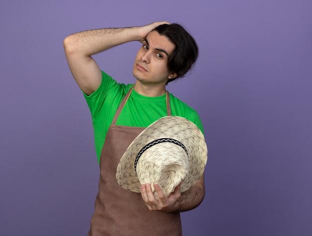 Junger männlicher gärtner in der uniform, die gartenhut hält, der hand auf kopf setzt