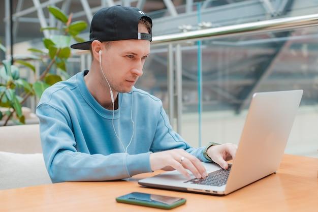 Junger männlicher geschäftsmann, der über online-projekt nachdenkt, laptop-arbeitscafé sucht, lösung nachdenkt, schreibtisch mit computer sitzt, student auf der suche nach einem neuen inspirationsbüro für ideen