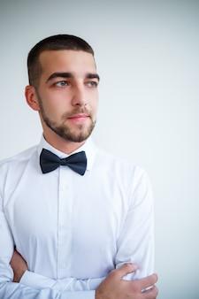 Junger männlicher geschäftsmann in einem weißen hemd mit kurzem bart trägt eine schwarze fliege