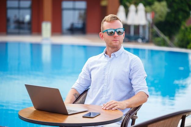 Junger männlicher geschäftsmann mit dem laptop, der am pool sitzt. offener arbeitsplatz. freiberufler-konzept. online einkaufen. ferienarbeit
