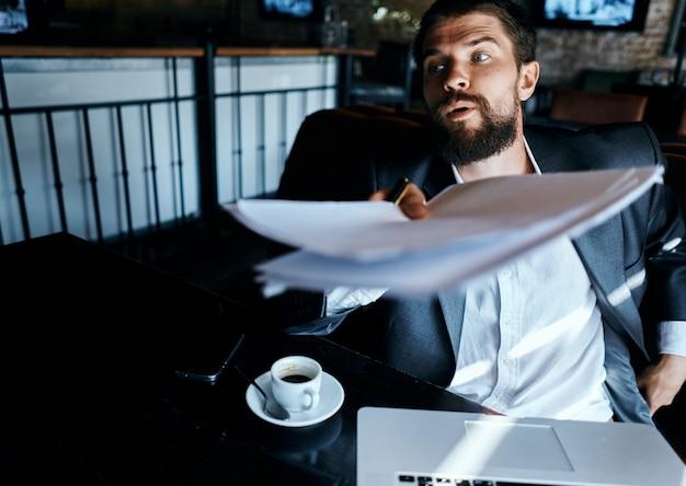 Junger männlicher geschäftsmann sitzt an einem tisch mit papieren und trinkt kaffee, schaut aus dem fenster