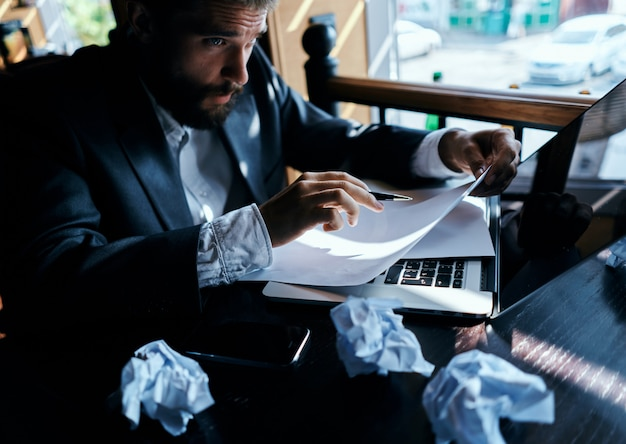 Junger männlicher geschäftsmann sitzt an einem tisch mit papieren und trinkt kaffee