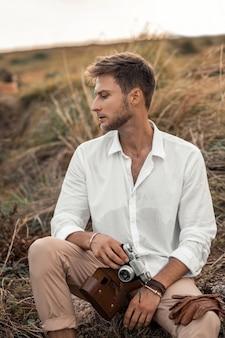 Junger männlicher hippie in einem weißen hemd mit alter kamera in seinen händen, die in der natur aufwerfen. erkunde unbekannt und sieh cool aus in einer seltsamen szenerie.