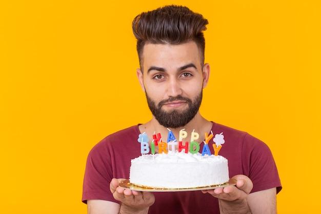 Junger männlicher hipster mit einem bart, der einen kuchen mit der inschrift alles gute zum geburtstag glückwünsche hält