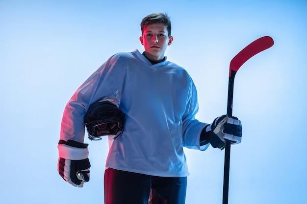 Junger männlicher hockeyspieler mit dem stock auf weißer wand im neonlicht