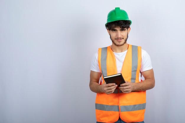 Junger männlicher ingenieur im grünen helm, der notizbuch auf weißem hintergrund hält. hochwertiges foto