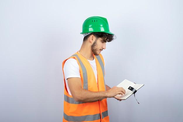 Junger männlicher ingenieur im grünen helm, der notizen auf weißem hintergrund liest. hochwertiges foto