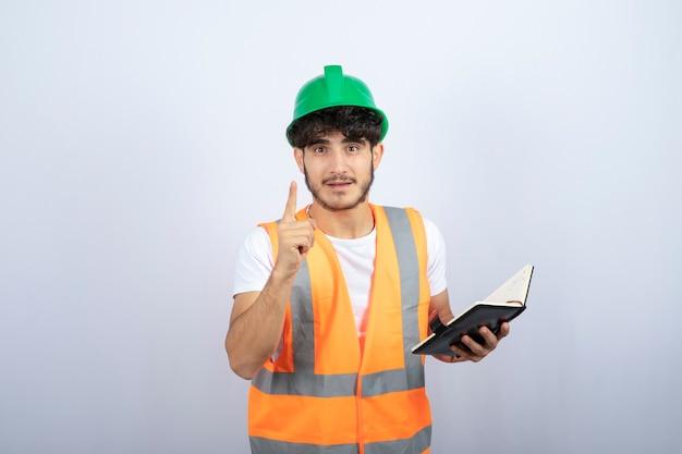 Junger männlicher ingenieur im grünen helm, der über sein projekt auf weißem hintergrund spricht. hochwertiges foto