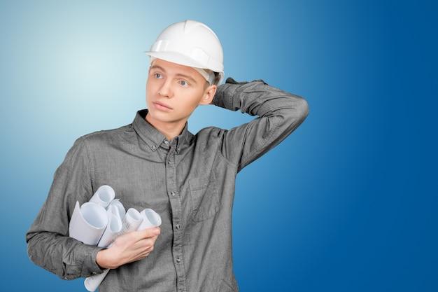 Junger männlicher ingenieur mit dem sturzhelm, der pläne hält