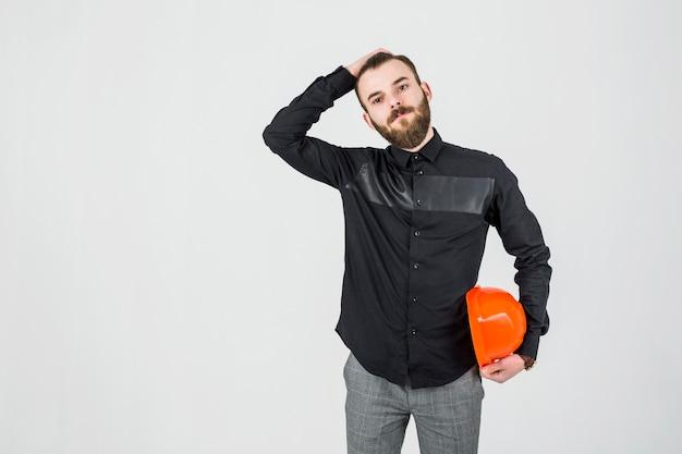 Junger männlicher ingenieur mit der hand auf seinem kopf, der hardhat hält